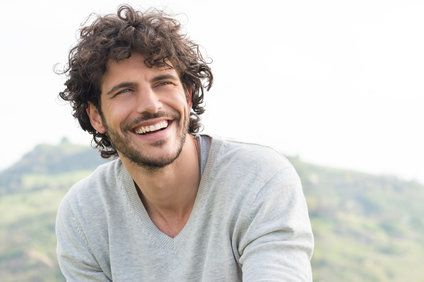 Dark-haired man smiling outdoors