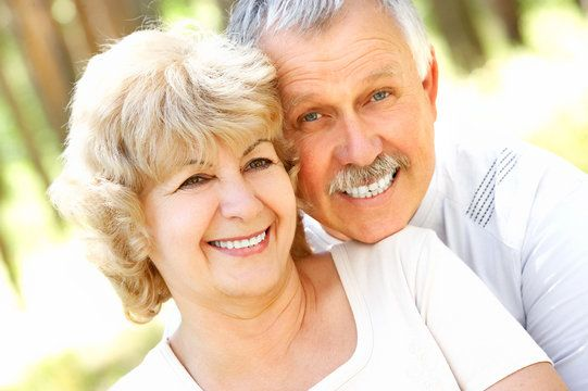 Middle-aged Caucasian couple smiling and laughing with husband resting chin on wife's shoulder
