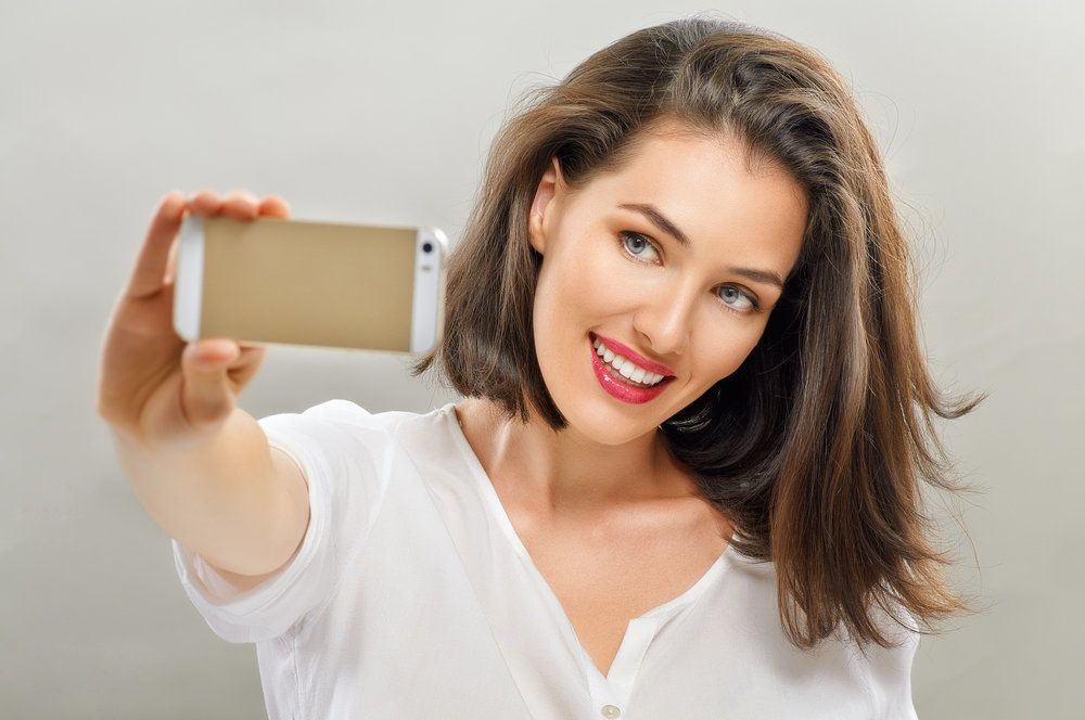 A woman with a bright, white smile taking a selfie