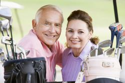 An elderly couple wearing pastels smiles while posing behind their golf clubs.