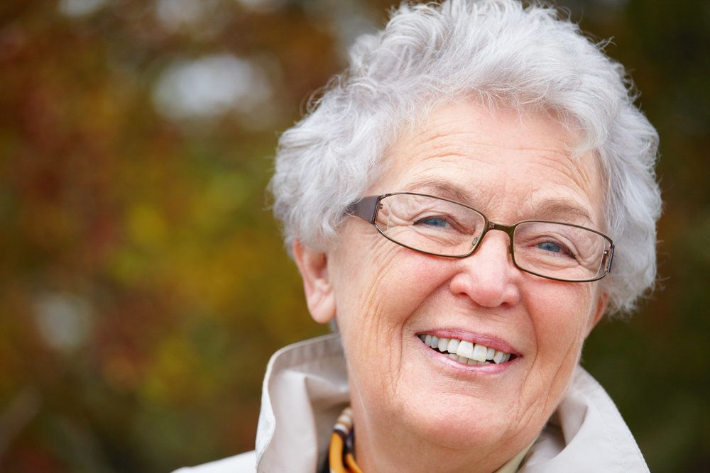 An older woman with dentures smiles happily