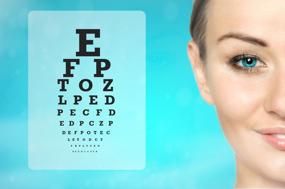 A woman smiling next to a Snellen eye chart