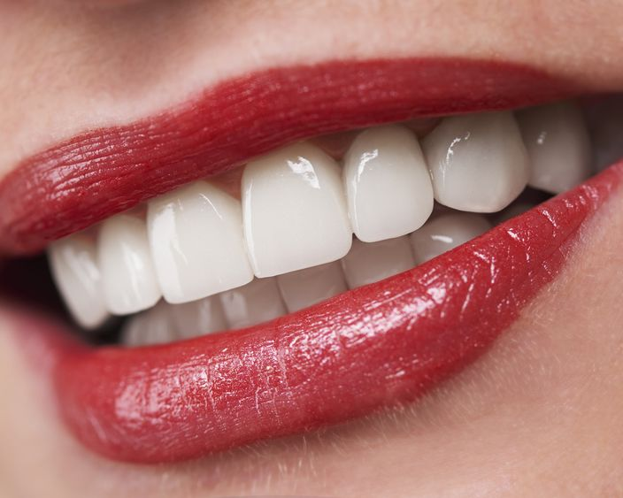 Extreme close up of woman's white teeth and red lipstick