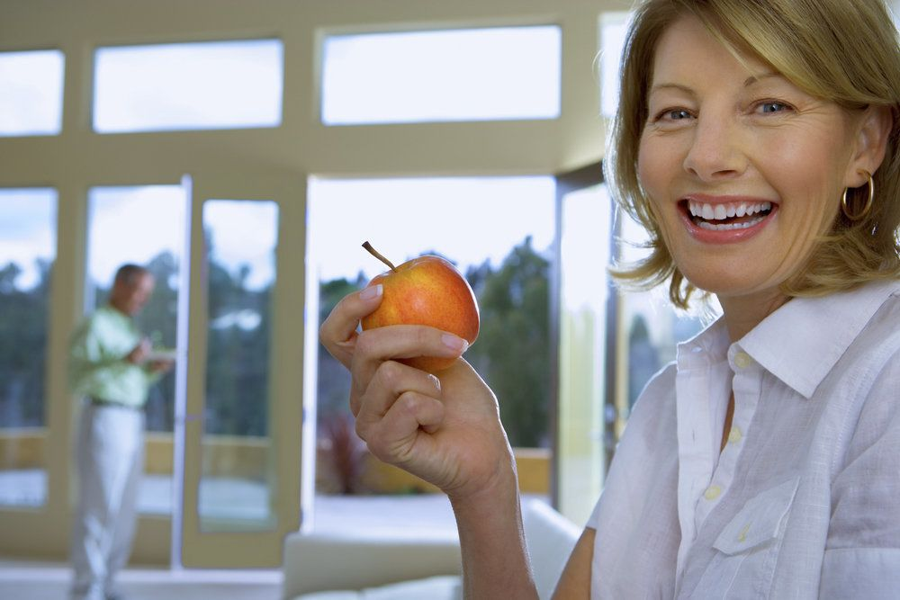 Smiling woman about to eat an apple