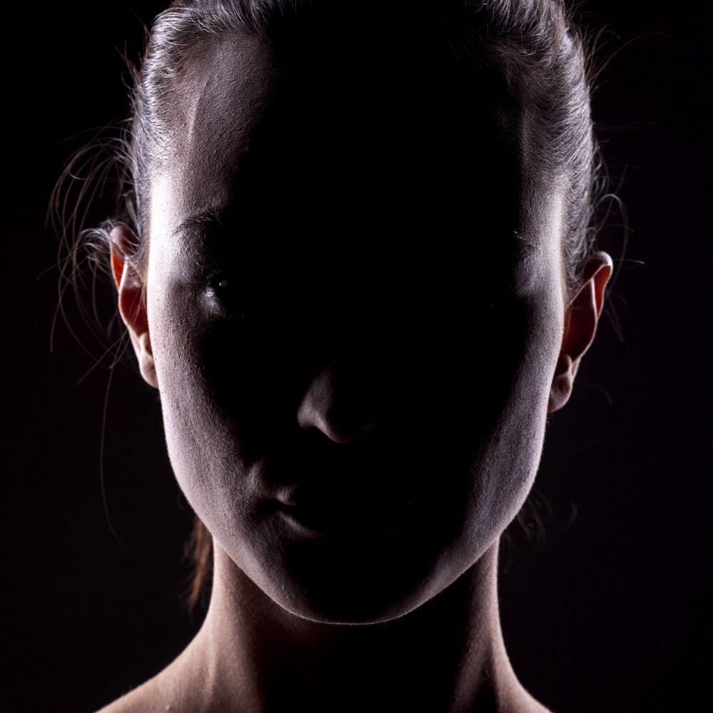A woman's face covered in shadow