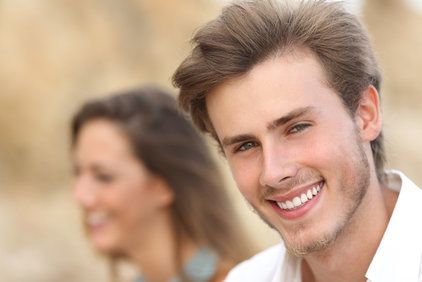 Handsome man close up portrait with a perfect white tooth and smile with a girl in the background