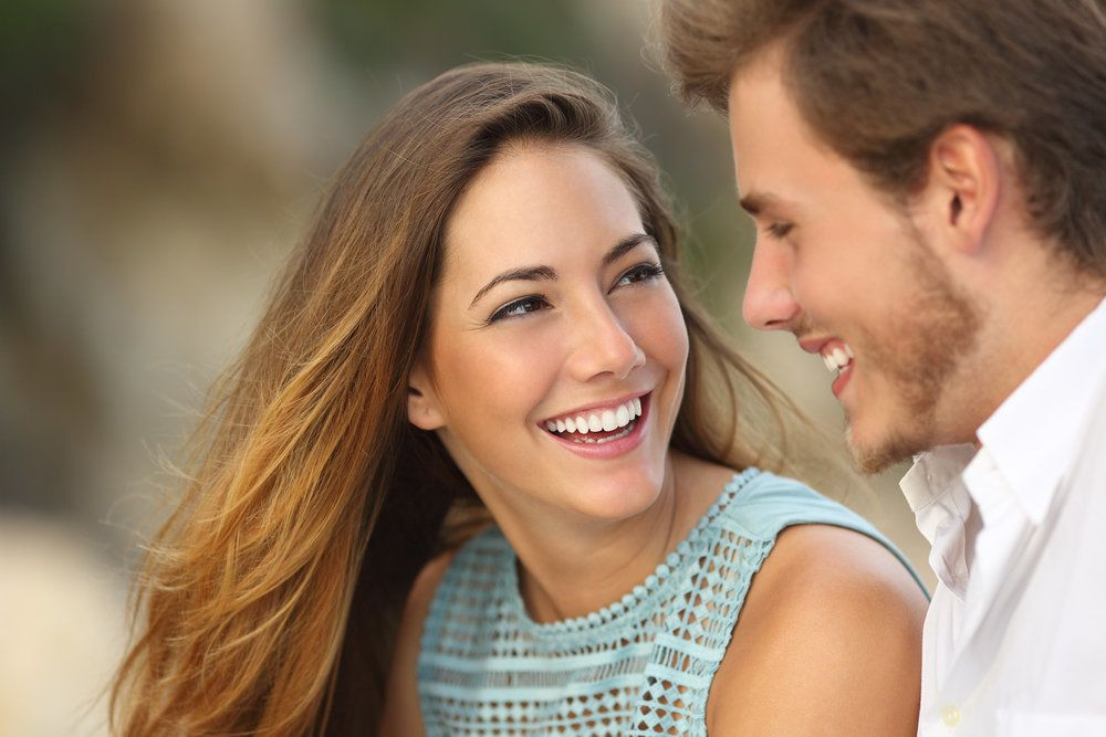 Young woman smiling at her boyfriend, her smile straight and uniform thanks to instant orthodontics with porcelain veneers