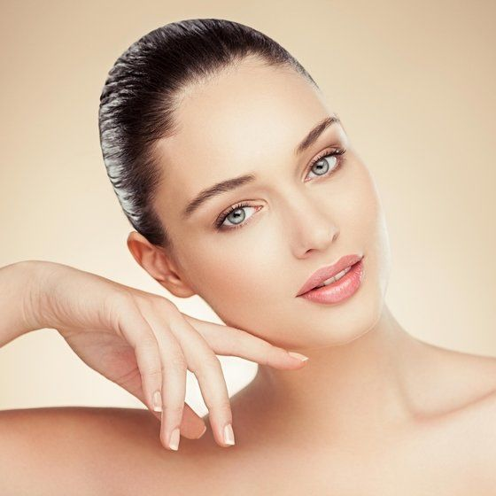 Woman with smooth skin and hair slicked tightly back resting cheek on finger