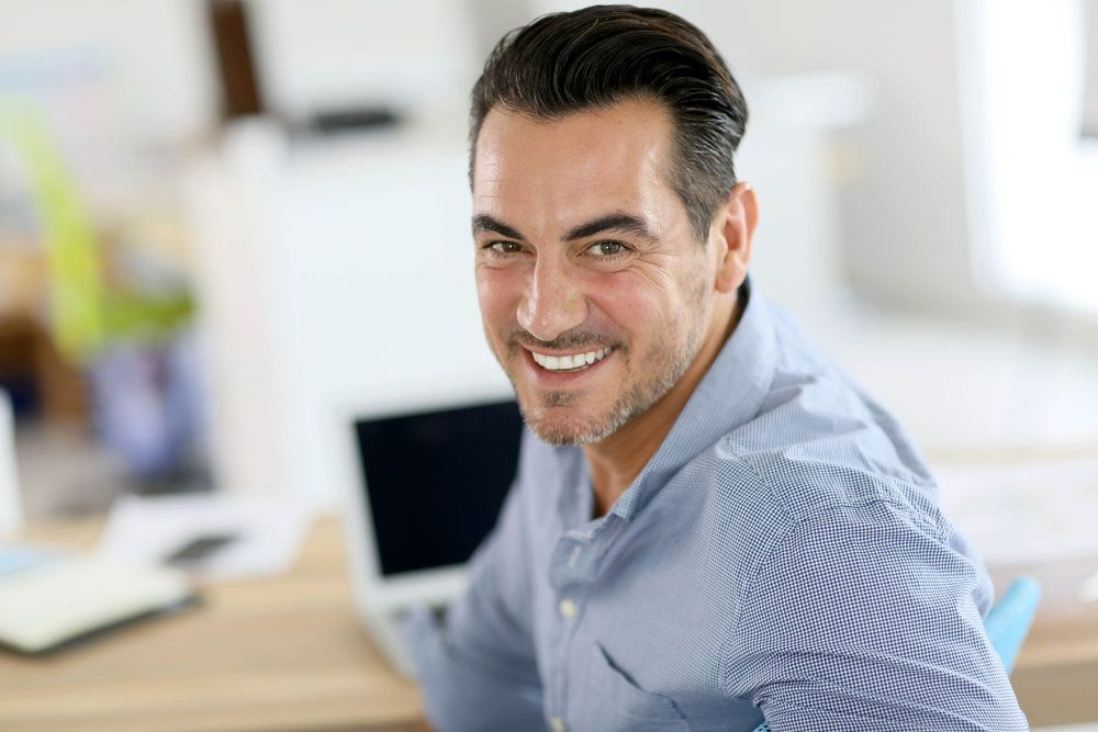 Smiling man sitting at his desk