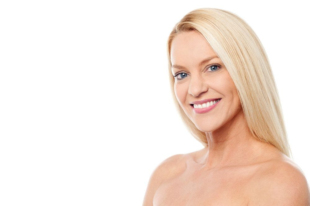 A woman smiling broadly, her neck skin smooth and rejuvenated after neck lift surgery