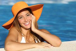 A young girl wearing a sun hat at the side of a pool, smiling to reveal her new porcelain veneers