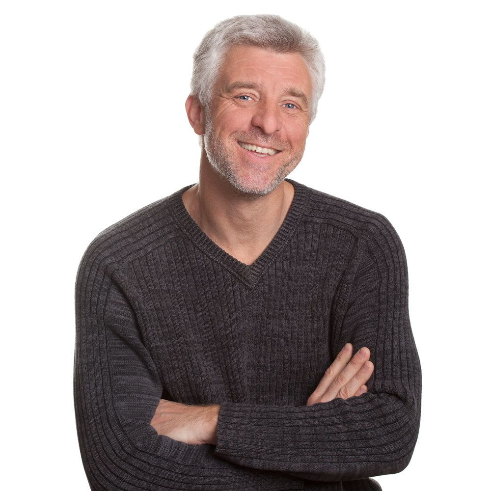 A smiling grey-haired man wearing a sweater