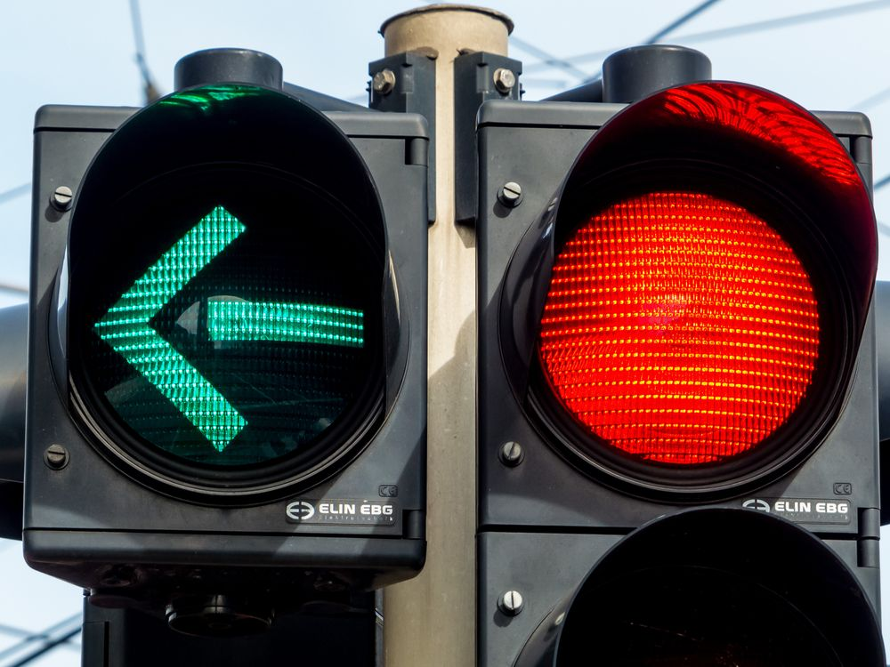 A traffic signal with a left turn and red light