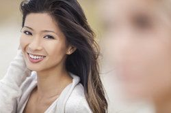 A young woman smiling to reveal her smile made over with LUMINEERS®