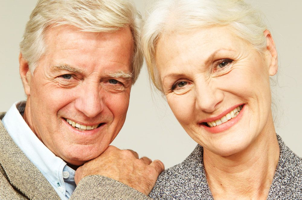 A man and woman lean in smiling.