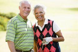 An elderly couple enjoying golf.