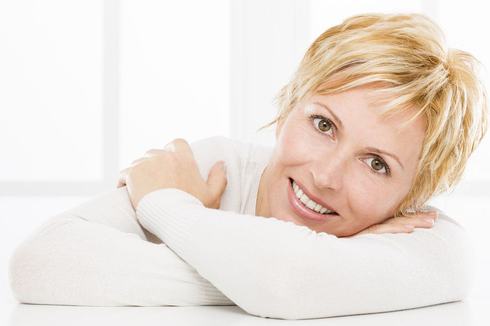 A woman with healthy, white teeth smiling while resting her head on her arms