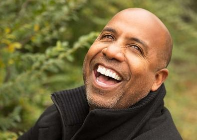 A balding man's healthy smile
