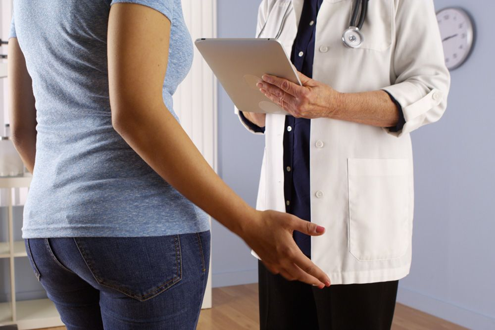 Woman in jeans and blue shirt talking with doctor in white coat who is holding a tablet