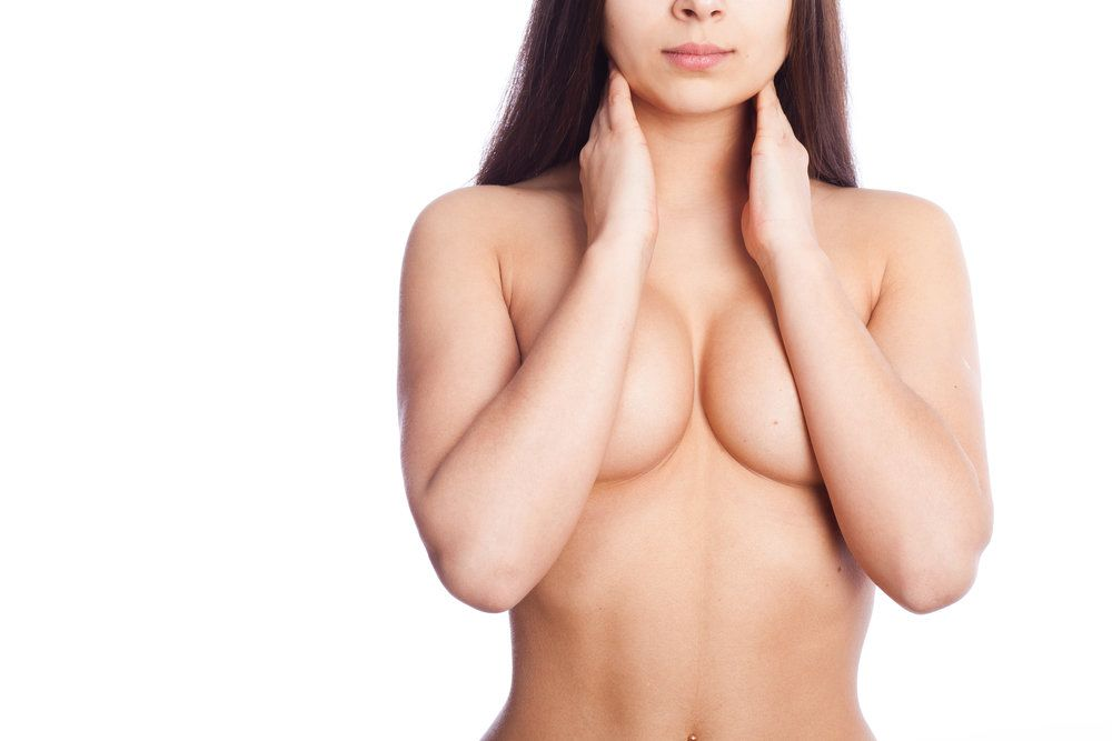 Close-up of a nude woman's midsection, her arms concealing her nipples after breast augmentation