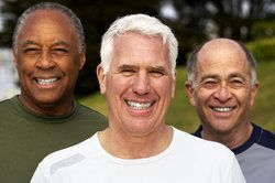 Three older men smiling outdoors