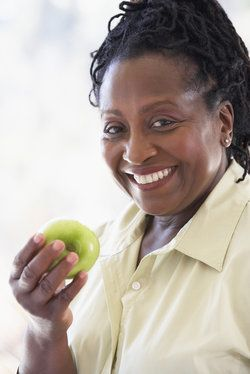 A middle-aged woman wearing a cream colored shirt holds a green apple and smiles.