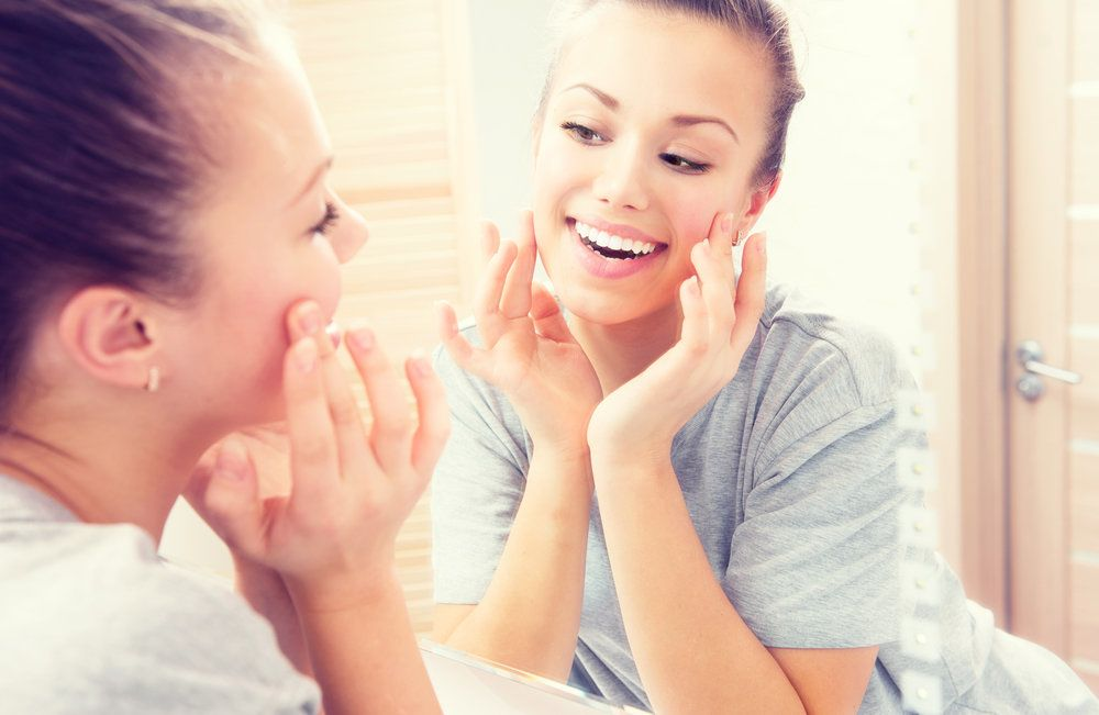 Woman touching her cheeks while looking in the mirror