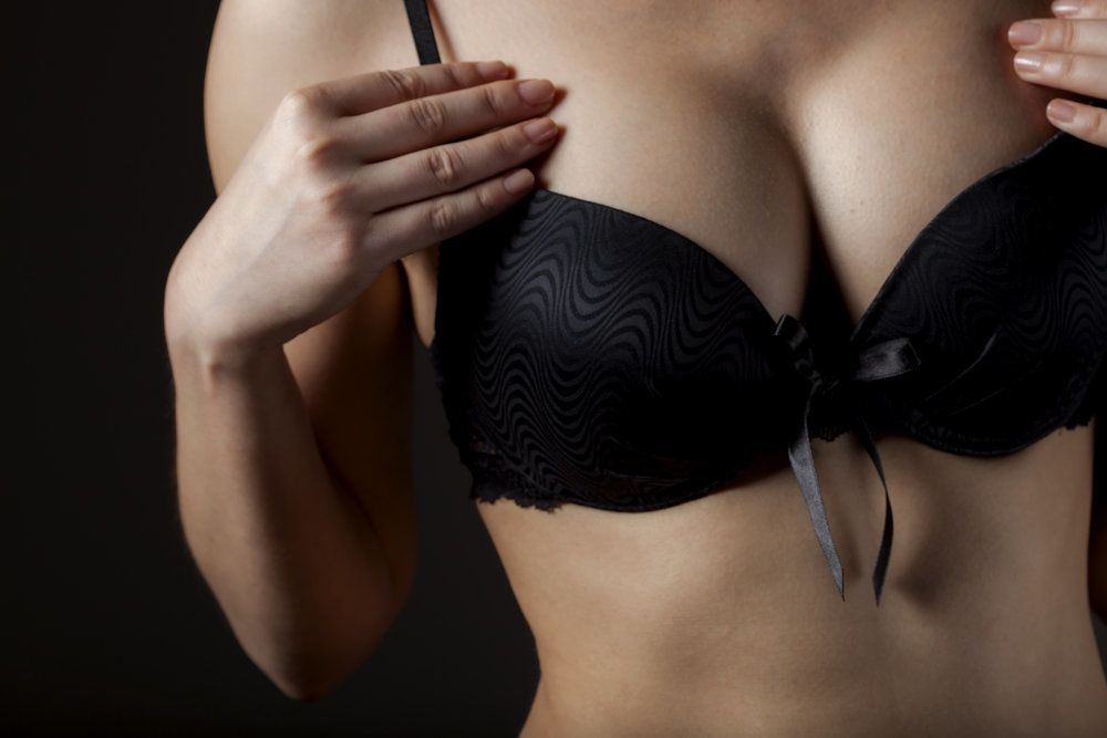 Close-up of a woman's bust, concealed by a black bra, after breast lift surgery