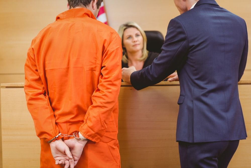 Man in orange jumpsuit with attorney speaking to a judge