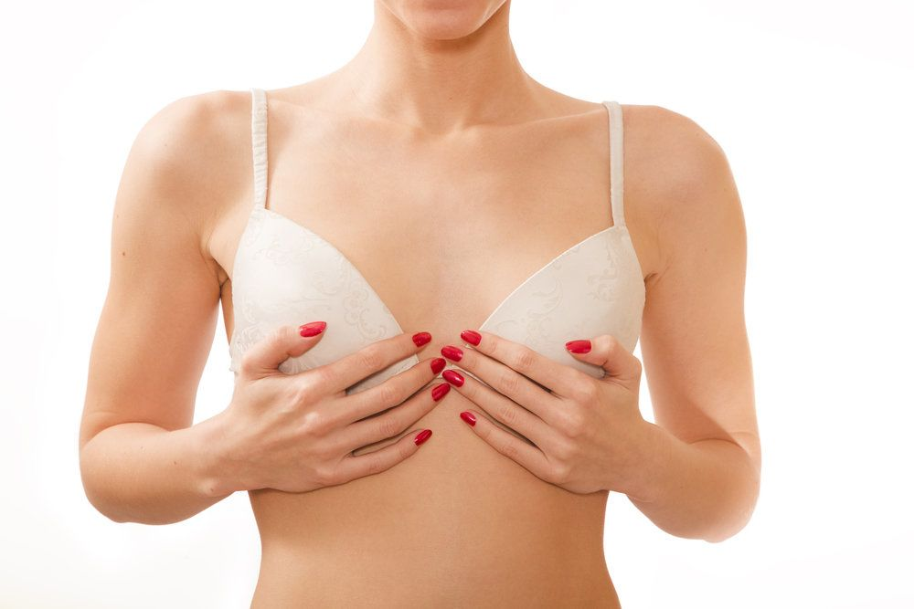 A woman with her hands over her bra, her breasts looking shapely after breast augmentation using the areolar incision technique