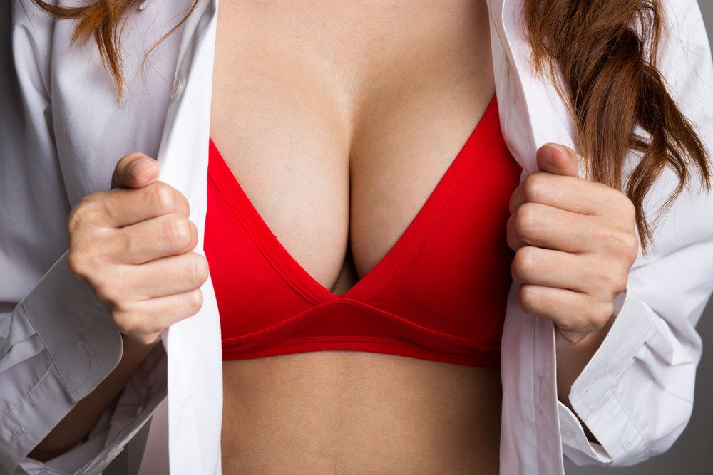 Close-up of a woman's breasts, contained within a red bra, after breast augmentation surgery