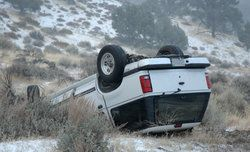 An overturned SUV in a ditch after an accident caused by road debris