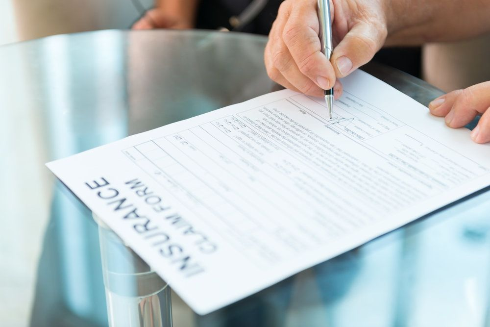 A person signing an insurance claim form after suffering property damage