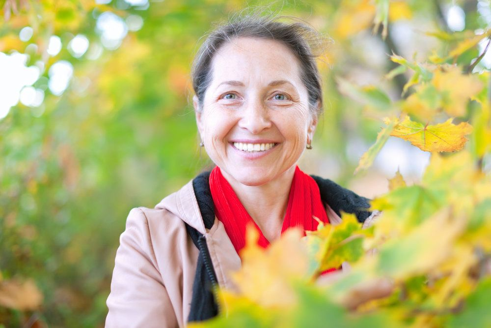 A woman smiles outdoors with foliage in the foreground.