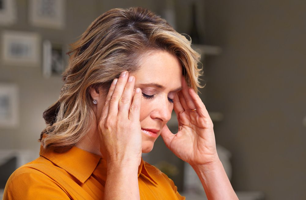 A woman holding the temples of her head due to a post-menopausal headache