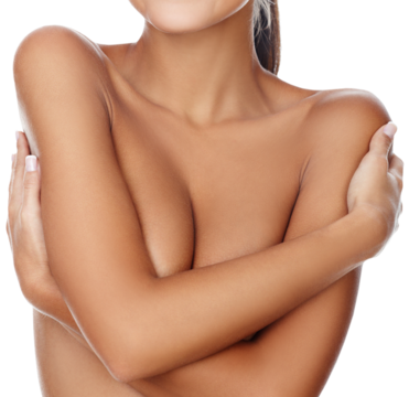 Woman crossing arms over naked chest and hugging shoulders