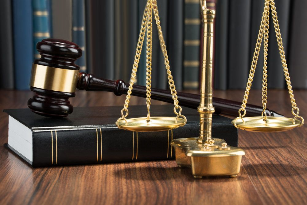 A gavel resting on a law book behind the scales of justice