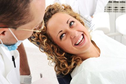 Woman smiling at her dentist during an appointment.