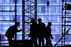 Silhouettes of construction workers in a dangerous setting where construction accidents frequently occur