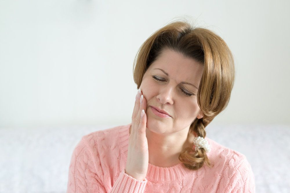 A woman clutching her jaw due to tooth pain