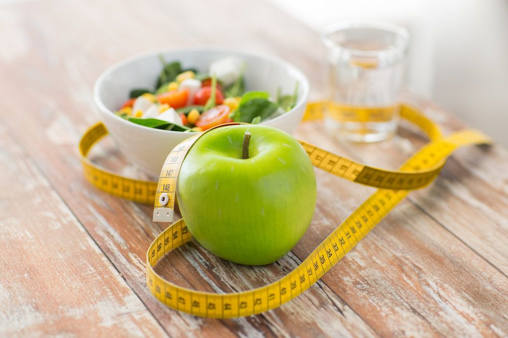 A green apple and measuring tape