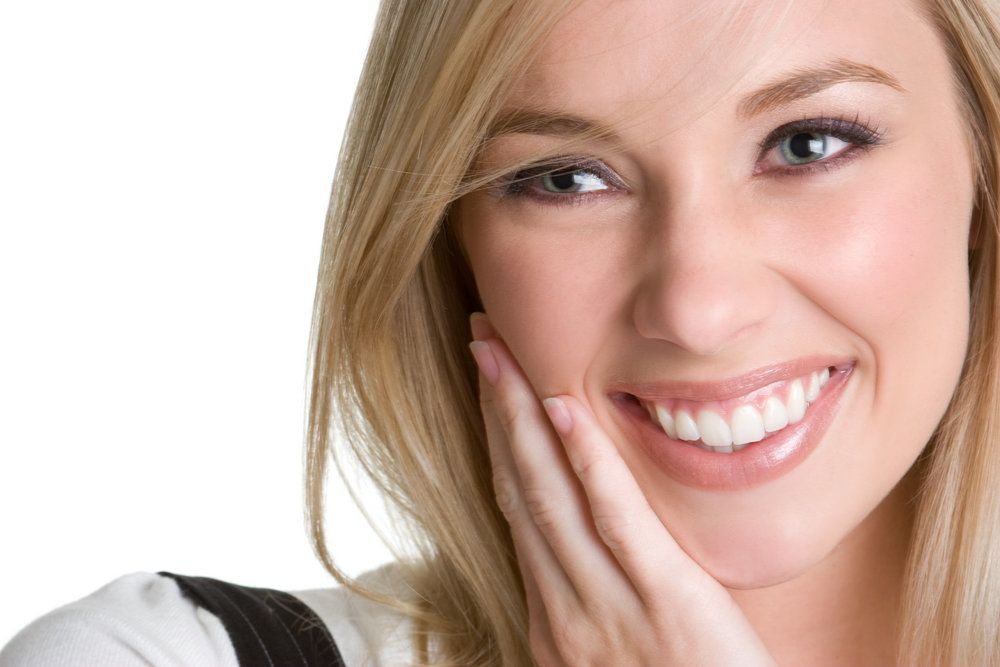 Smiling blond with smooth, youthful skin holding hand to cheek
