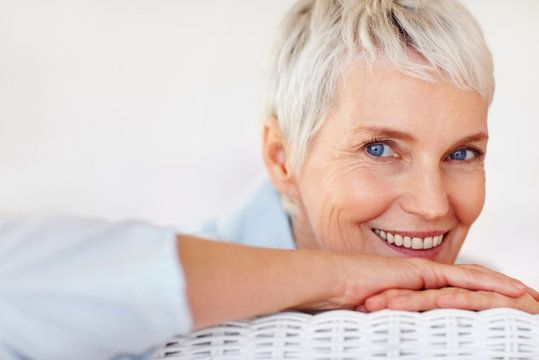 Elderly woman with pixie cut and bright blue eyes resting chin on folded hands