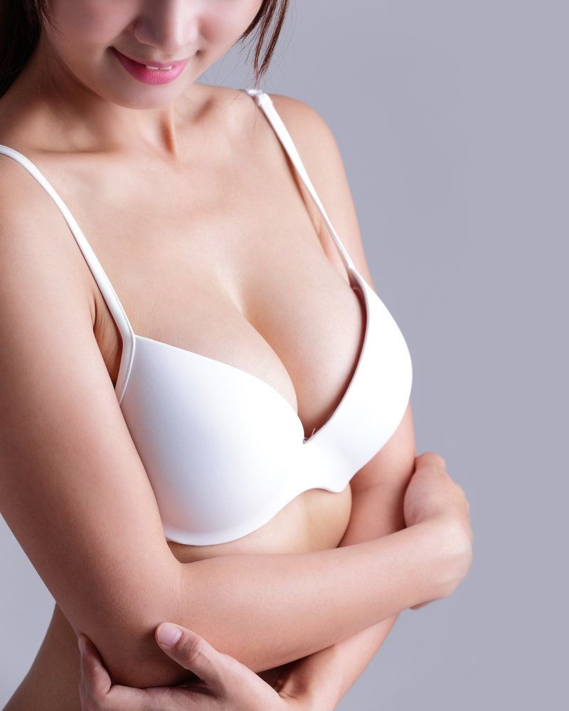 A woman with full breasts, wearing a bra