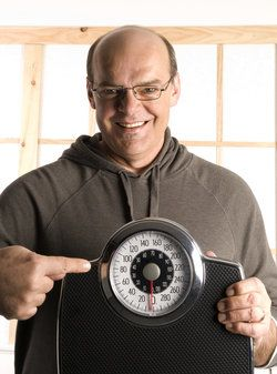 A bald man wearing a hoodie holds up a scale proudly.