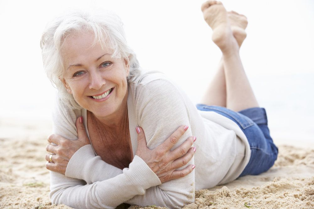 Smiling woman lying at the beach