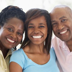 An older couple smiling with their teenaged granddaughter