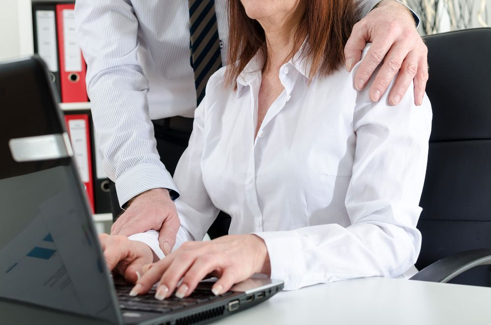 Businessman holding female employee's wrist suggestively