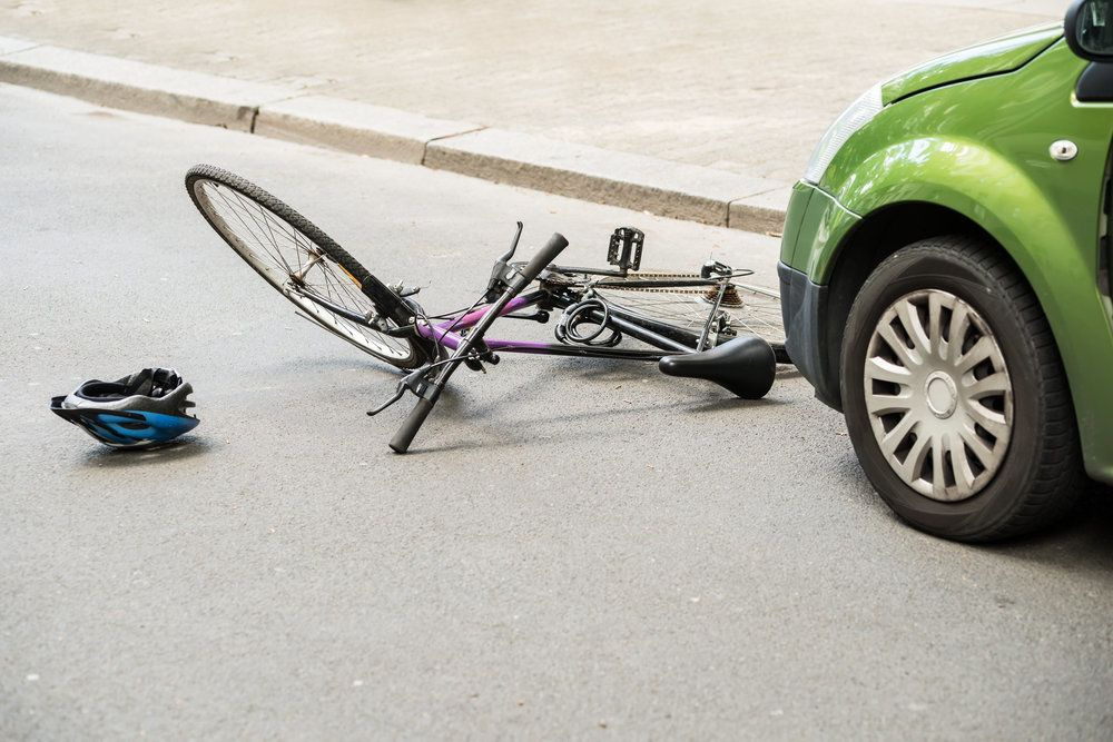 A bike lying on the ground in front of a car in the aftermath of a bicycle accident