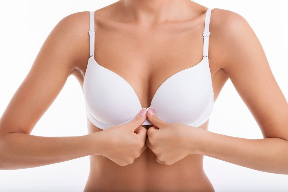 A woman holding the clasps of her bra together after breast augmentation recovery